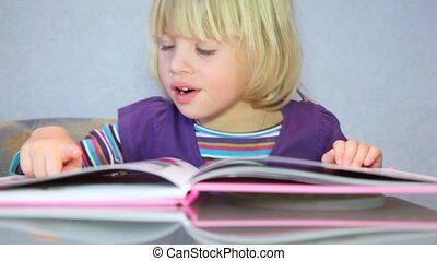 Little girl read a picture-book - Little blonde adorable...