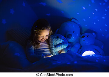 Little girl reading a book in bed. Dark bedroom with night ...