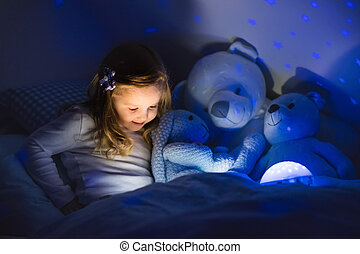 Little girl reading a book in bed. Dark bedroom with night...