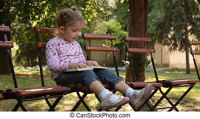 little girl reading a book in park