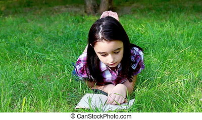 Little girl reading a book on grass