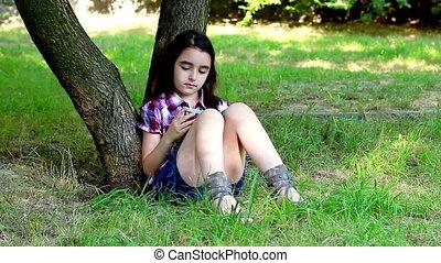 Little girl reading a book on grass