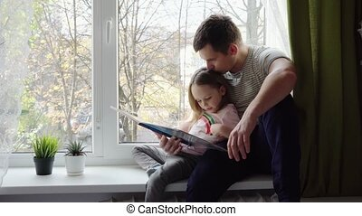 Little girl reading a book with his father