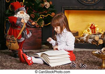 Little Girl reading a fairy tale toy Santa Claus.