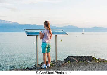 Little girl reading a map with Haute-Savoie Alps, standing by the lake Geneva in the evening