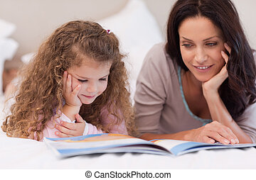 Little girl reading bedtime story with her mother - Little ...