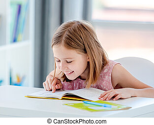 Little girl reading book in classroom