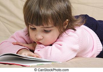 Little girl reading book on sofa