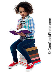 Little girl reading book using magnifying glass