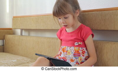 Little girl reading e-book on the sofa