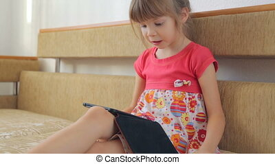 Little girl reading e-book on the sofa