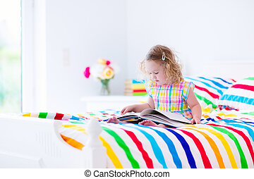 Little girl reading in bed - Toddler girl reading a book in...