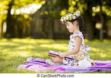 Little girl reading in the park