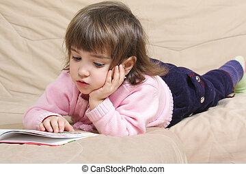 Little girl reading on sofa