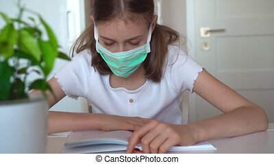 Little girl reading textbook during quarantine.