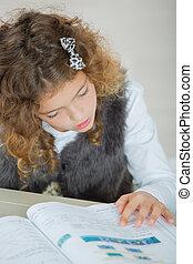 Little girl reading through a textbook