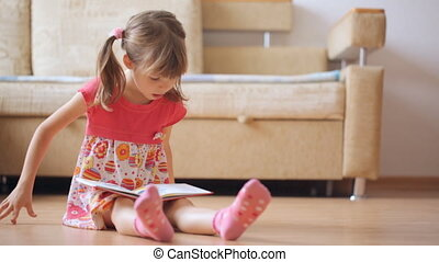 Little girl reads book sitting on the floor