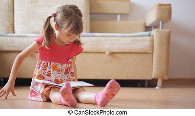 Little girl reads book sitting on the floor