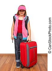 Little girl ready to travel with big red luggage