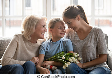 Little girl received from mother and grandmother flowers and gift