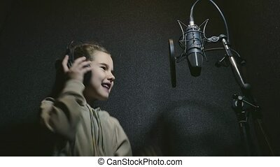little girl record writes a song sings into a microphone in...