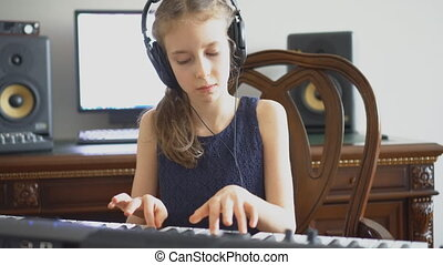 Little girl recording a song in home recording studio.