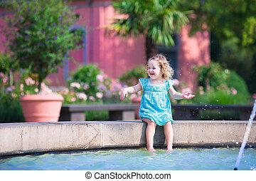 Little girl refreshing in fountain