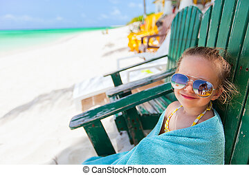 Little girl relaxing in colorful chair at beach
