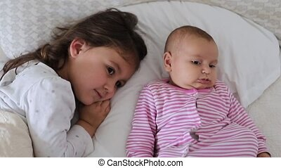 FHD Video of a little girl lying down on a bed next to her happy baby sister
