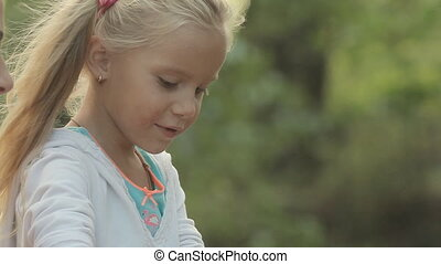 Little girl resting with his family in the forest and inflates soap bubbles