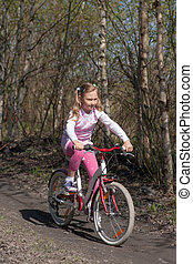 little girl rides a bicycle