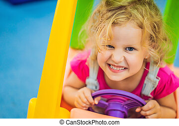 Little girl rides a toy colorful car