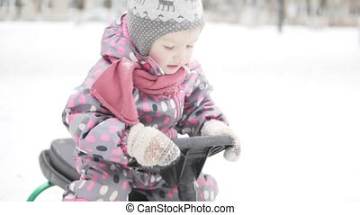little girl rides in the winter on a snow scooter
