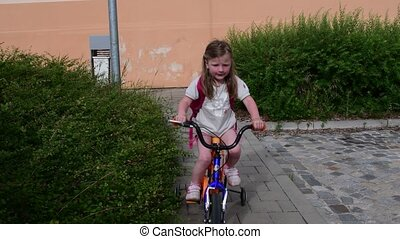 Little girl rides on bike. Summer time in the town
