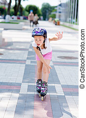 Little girl rides on roller skates at park