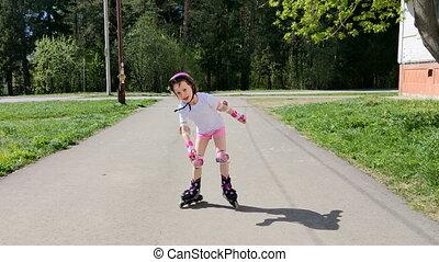 little girl rides roller skates outdoor
