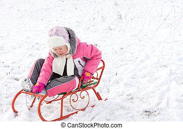 Little girl riding a toboggan in snow