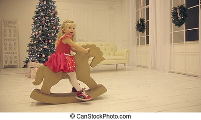 Little girl riding a toy in the New Year's Eve.