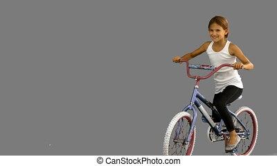 Little girl riding bike on grey screen in slow motion