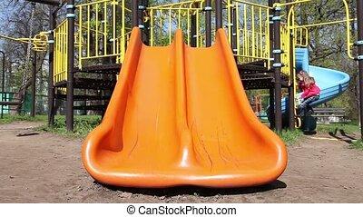 Little girl riding on a slide