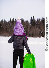 Little girl riding on dad outdoors in cold winter day