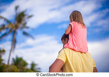 Little girl riding on her dad walking at tropical beach