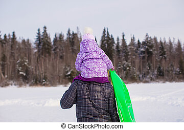 Little girl riding on young dad outdoors in cold winter day