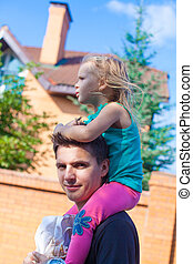Little girl riding on young dad outdoors
