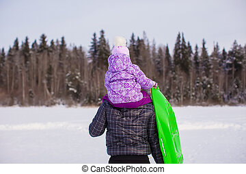 Little girl riding on young father outdoors in cold winter day
