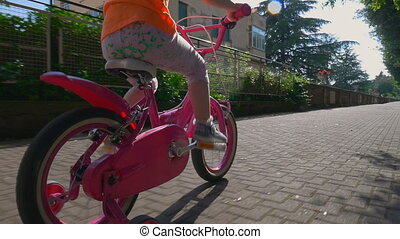 Little girl riding pink bicycle on bike path