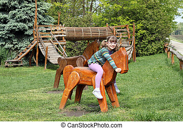 little girl riding wooden horse on playground