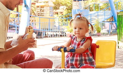 little girl rocks on swing father feeds with bun on play ground
