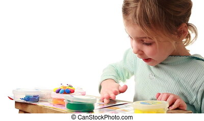 Little girl rolls on table small ball from plasticine