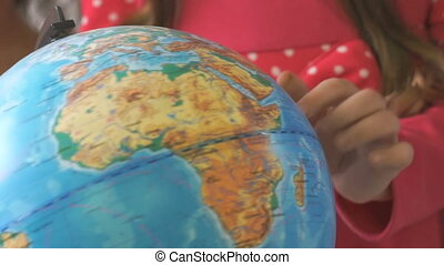 Little girl rotates the globe of world. Close-up